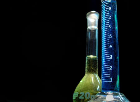Glass cylinder and balloon used in chemistry laboratory isolated on black background Standard-Bild