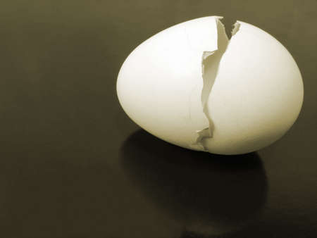 a broken egg shell on metallic background with reflection