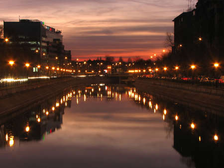Night cityscape with buildings on the banks of Dambovita river, Bucharest, Romania