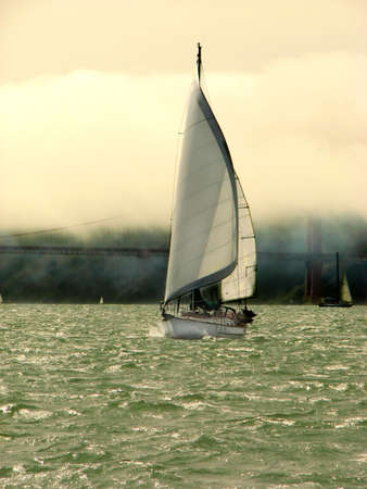 Yacht sailing in San Francisco Bay with the Golden Gate Bridge in the background, on foggy day Standard-Bild