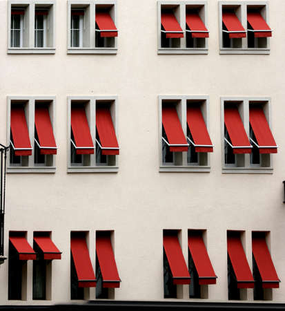 Windows with red window-shades on white wall