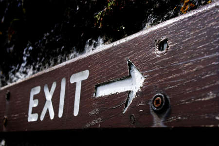 country side: Rustic exit sign written with white on a piece of wood