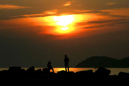 Sunset with people silhouettes on a rock beach at Thassos island, Greece photo