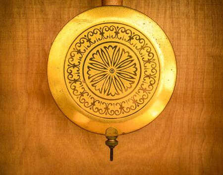 Golden pendulum from a vintage clock made in Russia former USSR (Soviet Union). Banque d'images