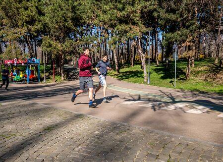 Buchares/Romania - 03.17.2020: Young men jogging in the park. People enjoying a run in the Alexandru Ioan Cuza Park.