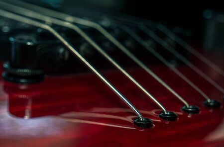 Close up with a guitar bridge and strings. Red guitar with blurred background. 免版税图像