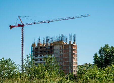 Construction crane and unfinished apartment or office building against blue sky. Construction site of a building Archivio Fotografico