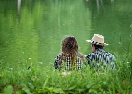 Couple relaxing on the edge of a lake in Youth Park, Bucharest.