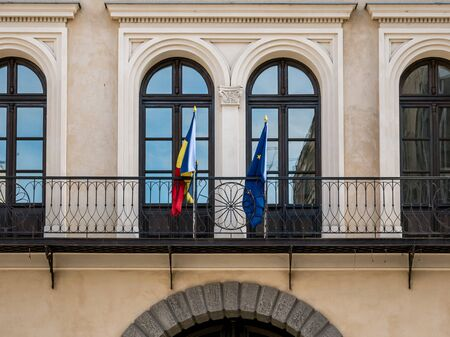 Architectural detail of a institution building in Bucharest. Romanian an European Union flags on a balcony in Romania.