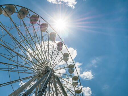 Amusement ride against blue sky. Close up with a white ferrys wheel. Stockfoto