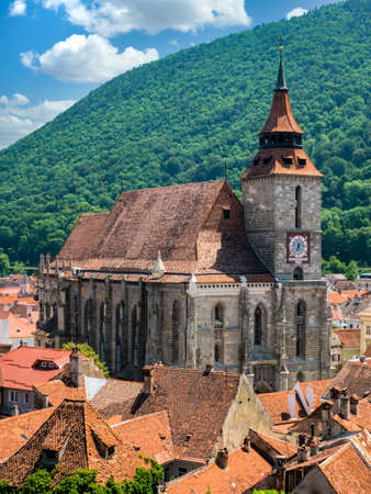 Brasov/Romania - 06.28.2020: The black church (Biserica Neagra) located in the center of Brasov with mount Tampa in the background.. Famous tourist attraction. Editorial