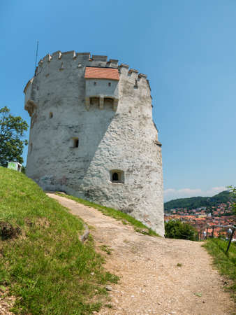Brasov/Romania - 06.28.2020: The white tower, a medieval tower defense guarding over Brasov city.