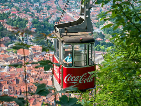 Brasov/Roamania - 06.28.2020: Man wearing a face mask in a cable car. Cable car with the city of Brasov in the background.