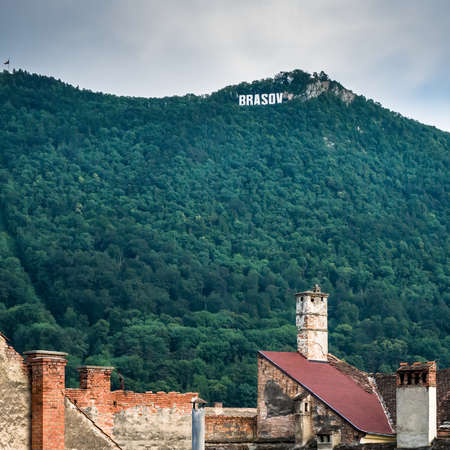 Brasov/Romania - 06.28.2020: Brasov written with big letters on Mount Tampa. Brasov sign with old roofs and chimneys in the foreground Editorial