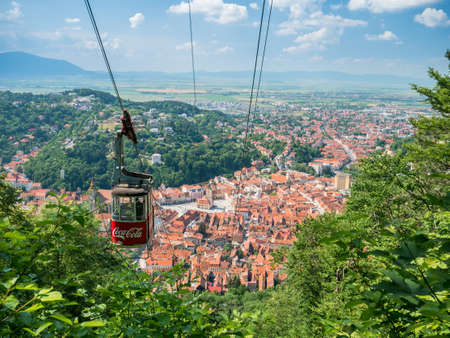 Brasov/Roamania - 06.28.2020: Cable car going to Mount Tampa summit with the city of Brasov in the background.