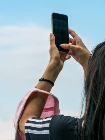 Girl taking a picture with her smartphone.