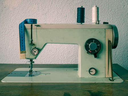 Old vinatge romanian sewing machine with sewing thread. Tailoring meter on a sewing machine.