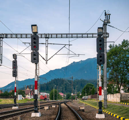 Railway traffic lights for trains with high mountains asa background in Busteni train station, Romania