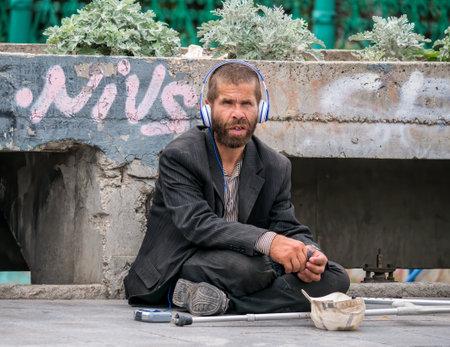 Bucharest/Romania - 07.25.2020: Homeless man or beggar sitting on the sidewalk and wearing headphones.