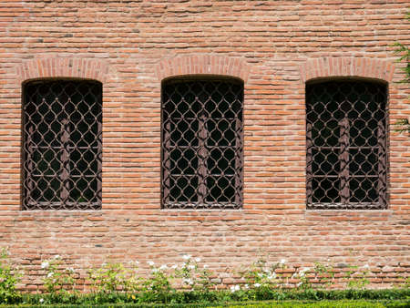 Outside wall of a medieval old building with three windows and bars. Brancovenesc or Romanian Renaissance architectural style.