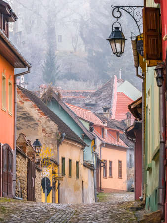 Sighisoara Romania - 11.26.2020: Scene with cobblestone streets and old buildings of Sighisoara Medieval Fortress, in Romania. Imagens