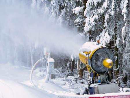 Snow cannon or snow gun throwing snow on the ski slopes in Predeal Mountain resort, in Romania.