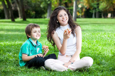 19's: A teenage asian caucasian girl with long curly brown hair with a boy laughing and having good time sitting on the green grass in the park  eatting a muffin Stock Photo