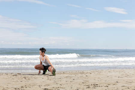 lunges: young woman with short hair doing sport lunges on the beach on a sunny day Stock Photo