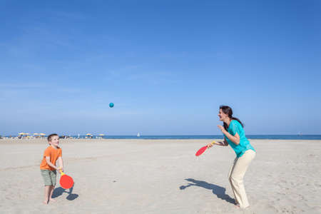 family mother and her son playing tennis on the beach photo
