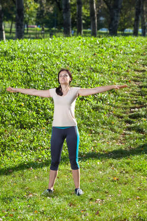 35 years: woman 35 years old doing breathing exercise in park