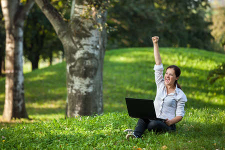 Excited mature woman wining holding fist up high screaming of happiness with laptop photo