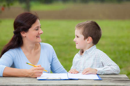 teaches: Young woman teacher teaches little young boy in white shirt writing or drawing with a pencil on a sheet of paper on wood table in the park Stock Photo