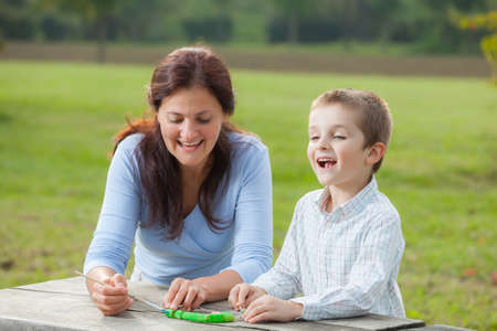 teaches: Young woman teacher teaches little young boy in white shirt painting with the brush to make artisanal pasta beads