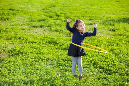 circle children: ragazza facendo esercizio con cerchio in plastica