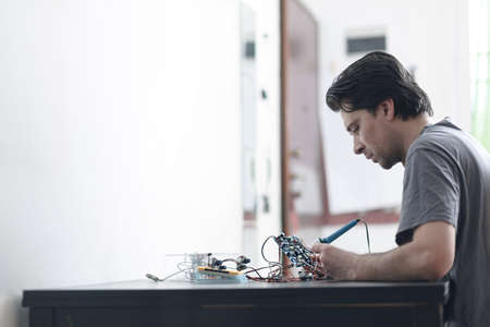 Young man making an electronic device soldering and adjusting the components