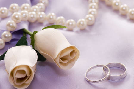 roses and wedding rings over satin Stock Photo