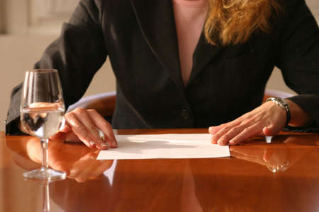 woman reading a paper holding a ball pen Stock Photo