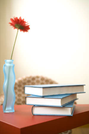volumes on a red table with flower on the side Stock Photo