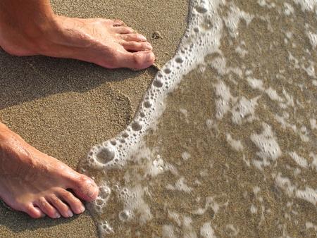 pies masculinos: pies en la orilla del mar Foto de archivo