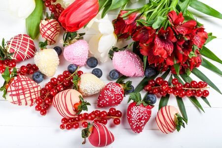 Chocolate dipped strawberries dessert mix ideal for Valentine's Day, Mother's Day, Woman's Day, brunch buffet, birthday or name day celebration party, romantic candy bar with spring March flowers Stock Photo