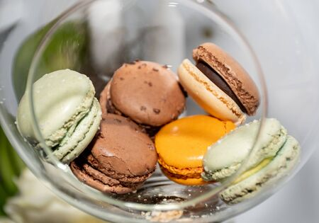 Many different colored macaroons in a festive Christmas transparent globe hanging in a festive decoration during brunch or catering event Stock Photo