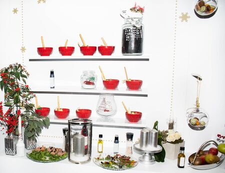 Tasty canapes salads red bowls in line appetizers, isolated on white shelves display background view, finger food snacks during hotel brunch buffet, food event catering display visual Stock Photo