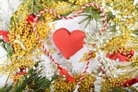 Floral background, spring concept, white wooden board, red ribbon, spring flowers like yellow Mimosa. Space for text, copy space in the center, middle empty Stock Photo