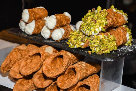 Cannoli are Italian pastries that originated on the island of Sicily and are today a staple of Sicilian cuisine. Cannoli consist of tube-shaped shells of fried pastry dough, filled with cream, ricotta