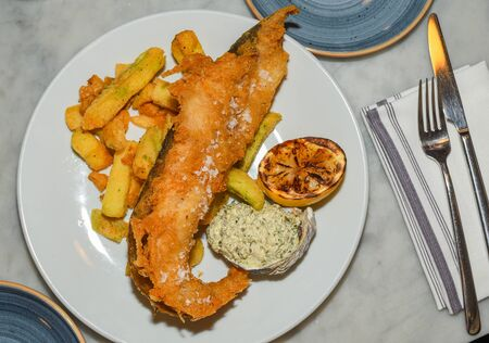British Traditional Fish and chips with mashed peas, tartar sauce on white plate served in a restaurant setting