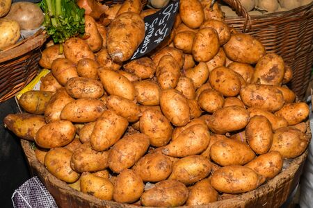 Fresh produce for sale at the farmer's market. Yellow young potatoes pile in a basket at grocery shop