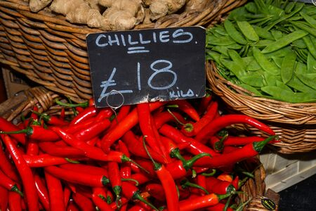 Red pepper for sale. Local produce for sale displayed at the market. Borough farmer's market in London. Organic and bio fresh healthy eating concept. Veggies, vegetables, herbs and spices, price tags
