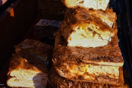 Traditional homemade artisanal apple or pumpkin pie served in a tray with powdered sugar on top to cover it. Romanian traditional bakery pastry recipe sold at food festival