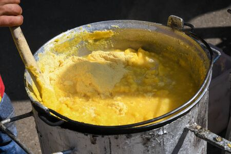"""Fresh polenta or """"mamaliga"""" cooking on large pot, chef stirring in pot over the fire, during street food festival, agricultural event. Golden maize corn powder mixed with water,gluten free alternative"""