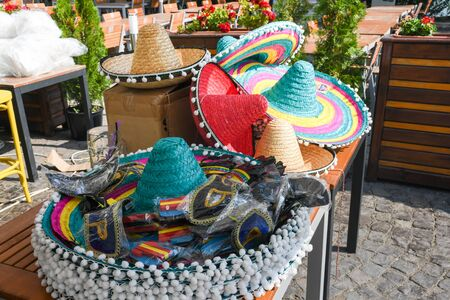 Stack of traditional Mexican hats, sombreros and accessories for mexican fiesta party, dress up, masquerade on an outdoor terrace hosting an authentic food festival